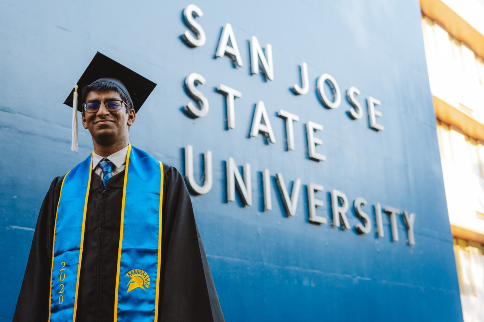 Me, wearing my cap and gown, in front of the San Jose State University sign